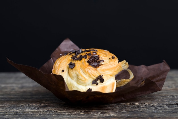 Sweet and delicious pastries with chocolate pieces, sweet wheat flour bun with chocolate pieces and chocolate filling, closeup