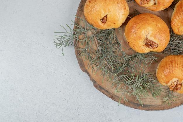 Сладкое вкусное круглое печенье с грецкими орехами на деревянной тарелке.
