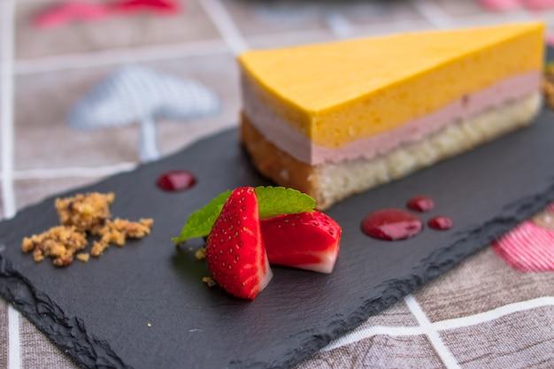 달콤한 맛있는 바닐라 망고 라즈베리 치즈 케이크는 신선한 딸기, 듀 베리, 민트와 함께 제공됩니다. 수플레 디저트.