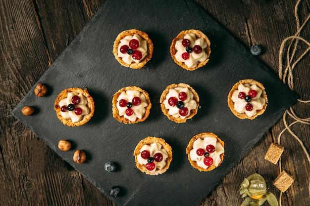 Сладкие десертные корзины со сливками и ягодами
