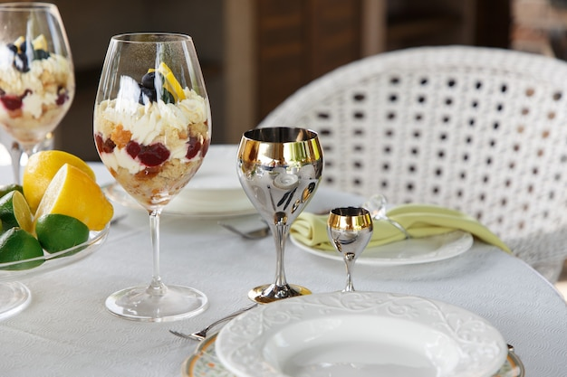 Sweet dessert in big glasses on table served for wedding banquet