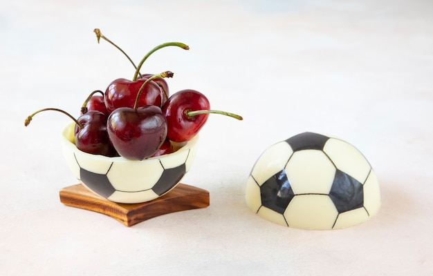 A sweet dessert for a fan of european football - a chocolate black and white ball made of two halves with ripe red cherries with sprigs on the table