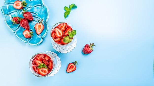 ガラスのベリーフルーツイチゴと青色の背景にホイップクリームの甘いデザート