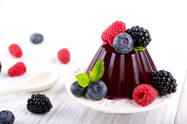 하얀 접시에 딸기 나무 딸기 블랙 베리 블루 베리와 달콤한 디저트 젤리 푸딩