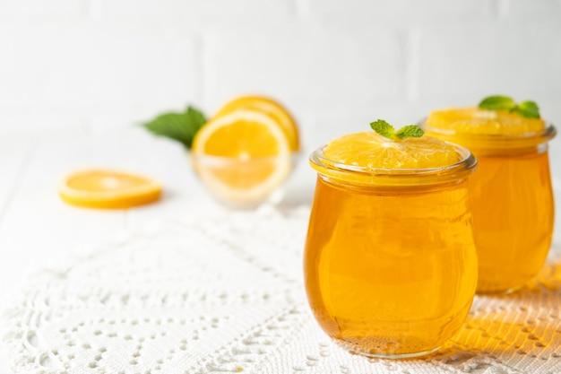 白い背景の上のガラスの瓶にオレンジ色の柑橘類と甘いデザートゼリープディング