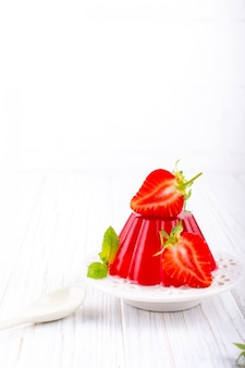 Sweet dessert jelly pudding with strawberries on white plate