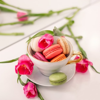 Sweet dessert macaroons in golden mug and pink tulips on white
