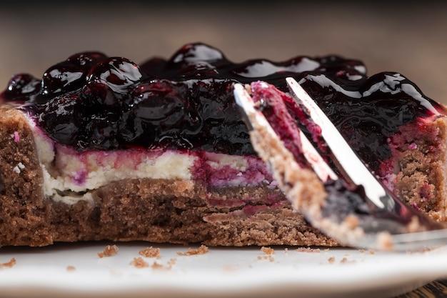 Сладкий десерт из молочных продуктов и ягод, торт со сливочным кремом и вареньем из черной смородины.