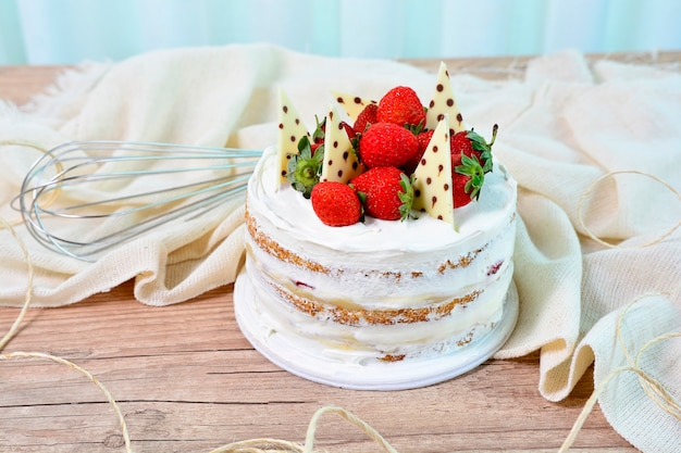 Sweet dessert naked cake with strawberries and chocolate pieces on topping on a rustic table