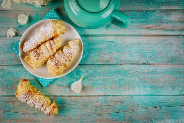 クリームと木製のテーブルにティーポットと甘いデザートのパイ生地