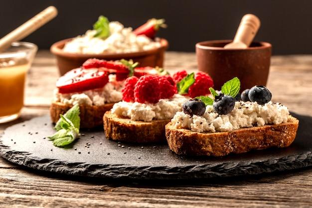 Сладкие десертные бутерброды со свежими ягодами черники и малины, сливочный сыр, мята и мед, фон рецепт еды. закрыть
