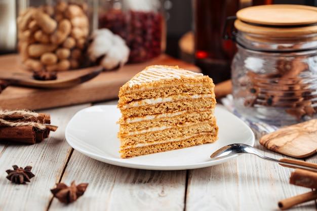 Сладкий десертный ломтик медового торта на тарелке