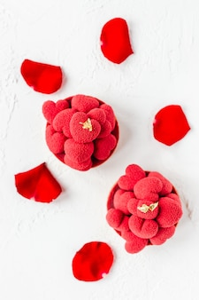 Sweet dessert tartelettes with red mousse hearts on top, decorated with red rose petals, top view