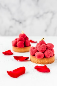 Sweet dessert tartelettes with red mousse hearts on top, decorated with red rose petals
