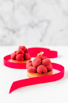 Sweet dessert tartelettes with red mousse hearts on top, decorated with a ribbon