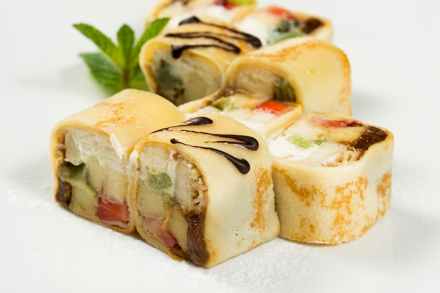プレートに巻き寿司のロールに包まれた甘いデザート
