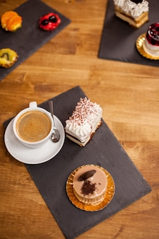 おいしいコーヒーの近くのコーヒーショップの木製のテーブルに甘いデザート。コーヒーショップで自家製デザート。おいしいチョコレートケーキ。