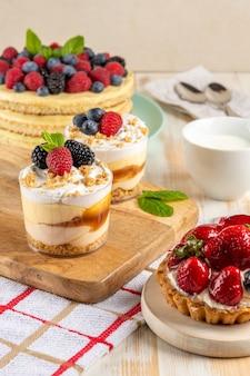 Сладкие десерты со свежими ягодами на деревянных фоне.