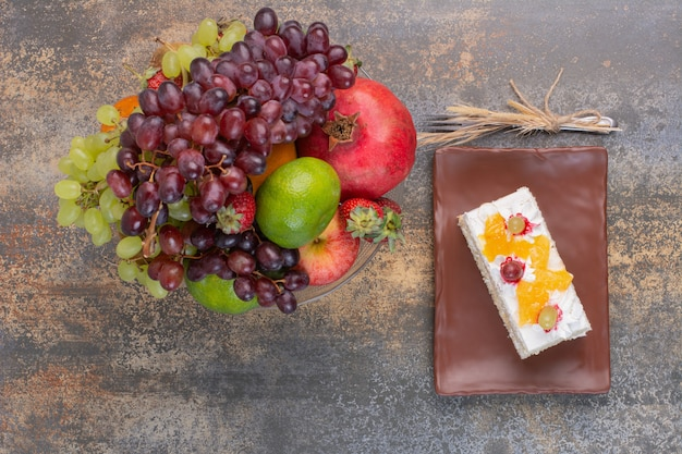 Sweet different fruits on glass plate with piece of cake on dark plate