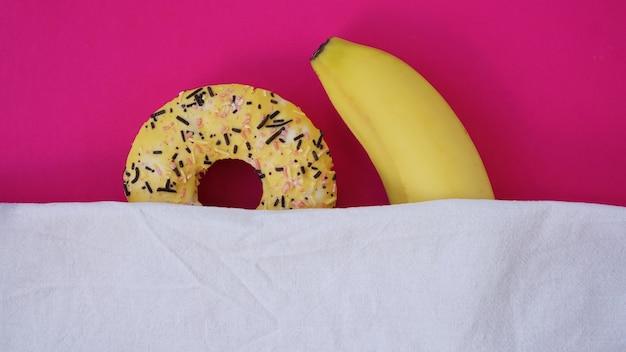 ピンク色の背景に甘いドーナツとバナナ。バナナはベッドでドーナツを抱きしめます