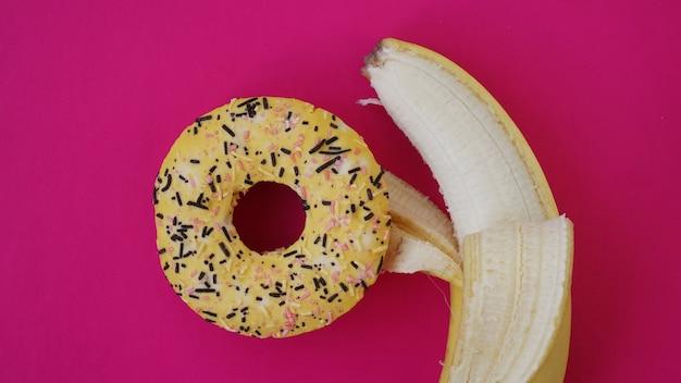 ピンク色の背景に甘いドーナツとバナナ。バナナがドーナツを抱きしめる
