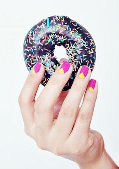 Сладкий пончик в руке Premium Фотографии