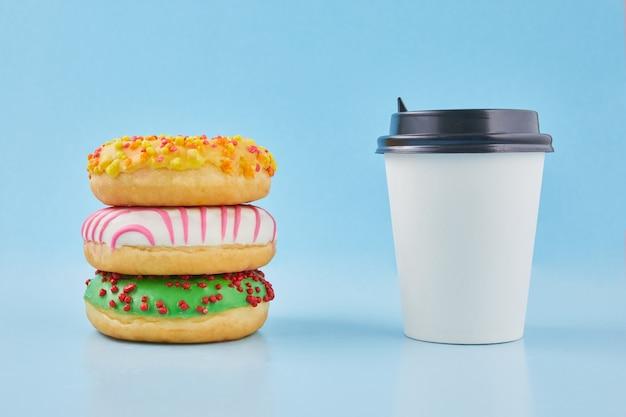 甘いドーナツまたは淹れたてのコーヒーまたは紅茶のホットカップとドーナツ。ドーナツ付きテイクアウト紙コップ。