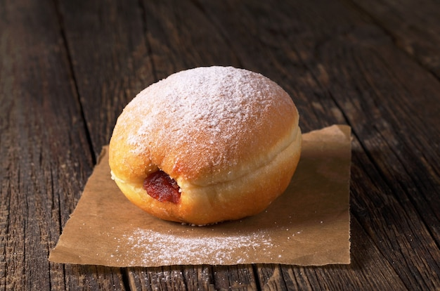 Sweet donut with jam on old wooden table close up