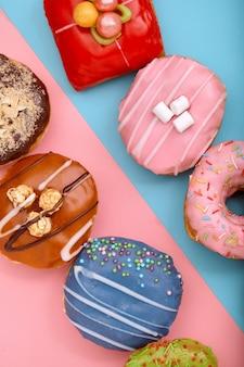Сладкие пончики на синий и розовый фон. ассорти пончики, границы цвета синий розовый фон.