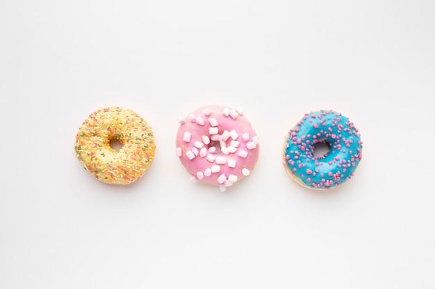 Сладкие пончики на простом фоне