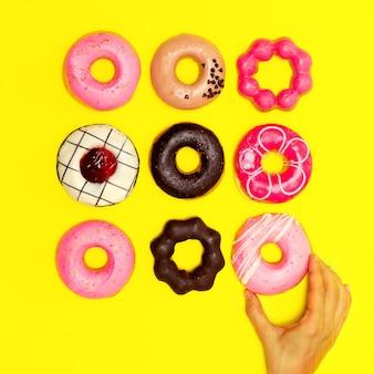 노란색 바탕에 달콤한 도넛이 있습니다. 플랫 레이 패스트 푸드 최소한의 예술