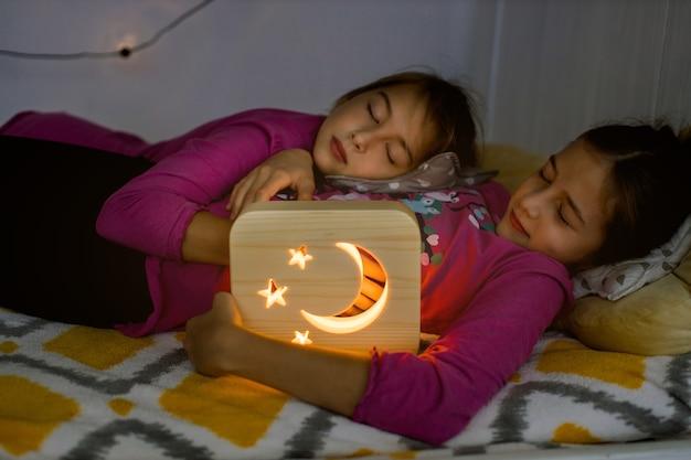 Сладких снов, спокойной ночи и промо-концепции ночников. крупным планом вид двух красивых 10-летних девочек-сестер, лежащих вместе в уютной постели с деревянной ночником и спящих или дремлящих.