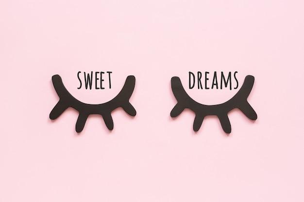Сладкие сны текст и декоративные черные деревянные ресницы, закрытые глаза на розовом фоне. концепция спокойной ночи.