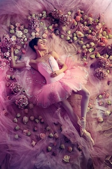 Sweet dreams. top view of beautiful young woman in pink ballet tutu surrounded by flowers. spring mood and tenderness in coral light.