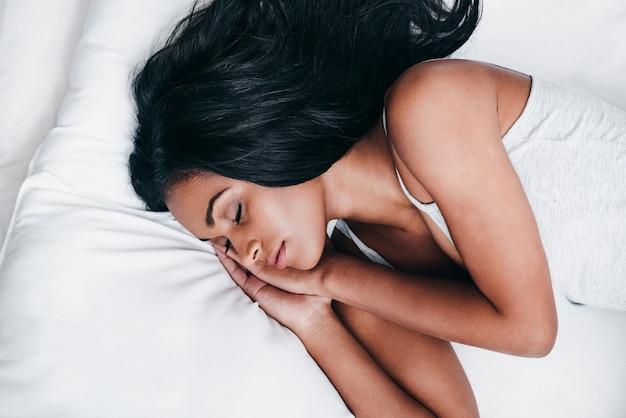 좋은 꿈 꿔. 침대에 누워 탱크 탑에 아름 다운 젊은 아프리카 여자의 상위 뷰 클로즈업