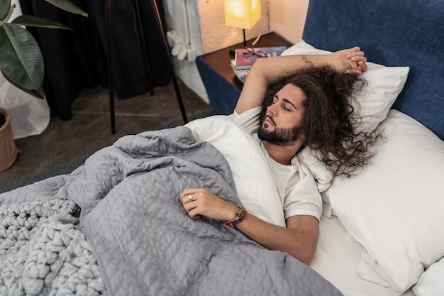 良い夢を。彼のベッドで休んでいるハンサムな眠そうな男のトップ ビュー