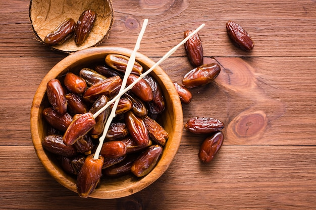 Sweet dried dates fruit in a wooden bowl on the table. top view