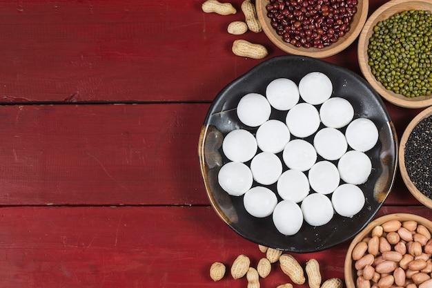 テーブルの上のボウルに甘い餃子、ang powまたは赤いパケットと金のインゴット