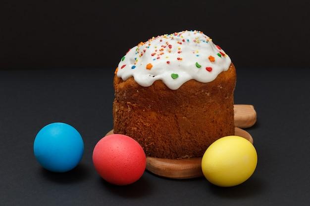 나무 커팅 보드와 다채로운 부활절 달걀에 달콤한 부활절 케이크