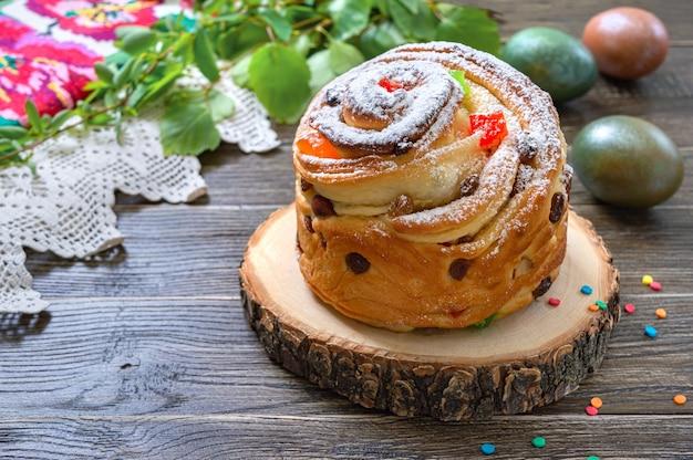 달콤한 부활절 케이크, 페인트 계란, 나무 테이블에 녹색 지점.
