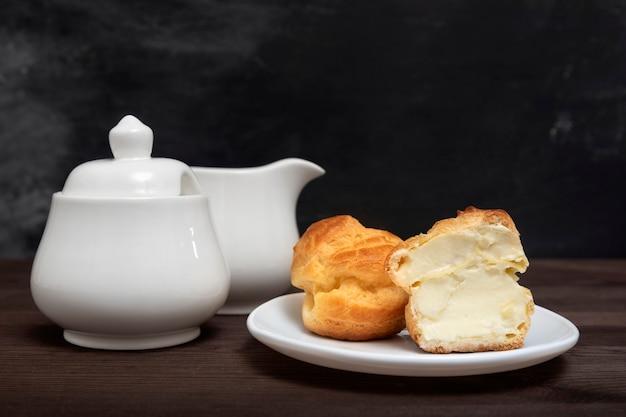 Сладкий торт эклер с кремовой начинкой на белой тарелке и чайном сервизе. сладости кондитерские. выпечка к чаю.