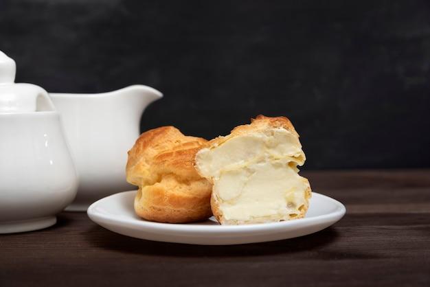 Сладкий торт эклер с кремовой начинкой на белой тарелке. кондитерские торты. закройте вверх. домашняя выпечка к чаю.
