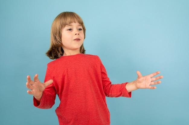 Сладкий европейский мальчик в красном свитере позирует на изолированном синем фоне студии.