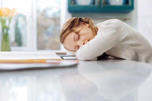 Милая белокурая маленькая школьница спит над своими книгами, сидя за столом и делая домашнее задание