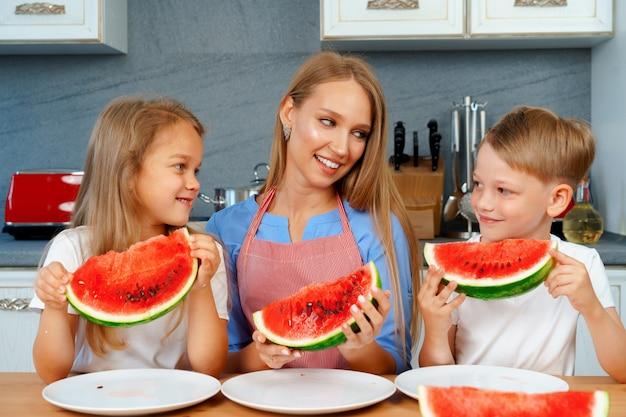 달콤한 가족, 어머니, 아이들이 부엌에서 수박을 먹고 즐겁고,