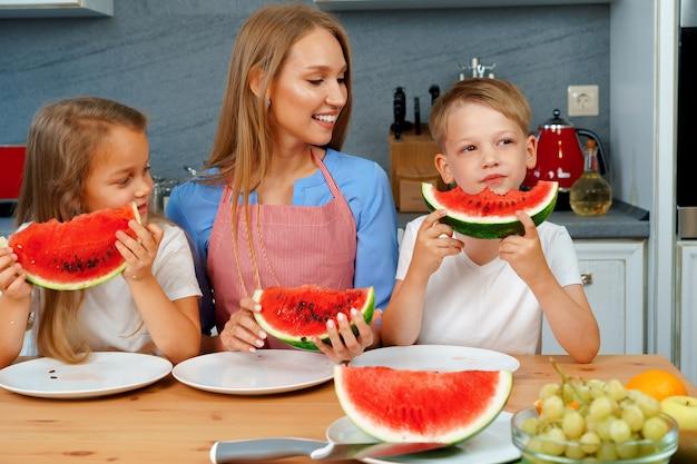 甘い家族、母親と彼女の子供たちが楽しんでキッチンでスイカを食べる