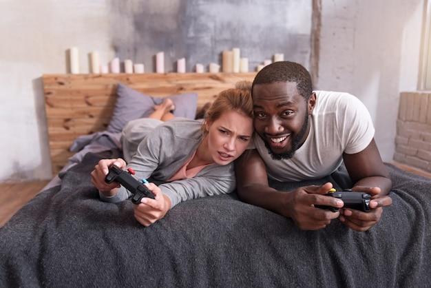 Сладкие семейные времена. обрадованная молодая пара из разных стран, наслаждающаяся видеоиграми и использующая консоль, лежа в постели.
