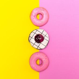 컬러 배경에 달콤한 패션 도넛입니다. 플랫 레이 패스트 푸드 최소한의 예술