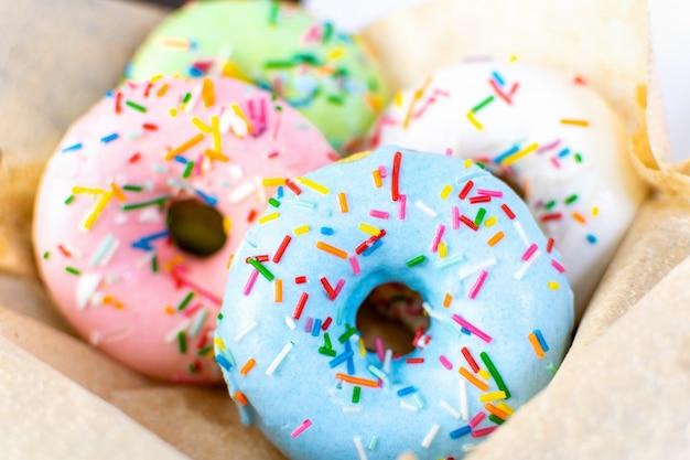 甘いファーストフード-さまざまな色のおいしいドーナツとペストリーの箱にさまざまな詰め物をクローズアップ。朝食においしいパン屋さんのデザート。