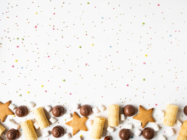 Sweet festive pastry border with chocolate, waffles, cookies, marshmallows and pastry topping on a white background.